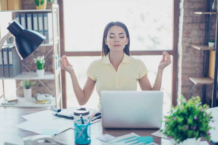 Female office worker meditating at her desk to reduce stress