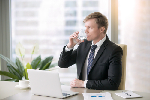 Professional man takes a drink of water